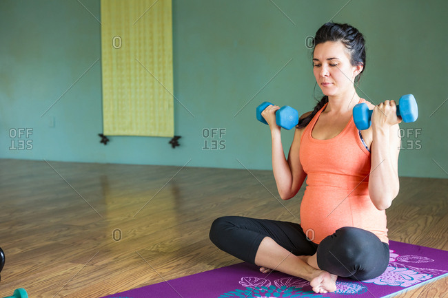 Mixed Race expectant mother lifting weights on exercise mat