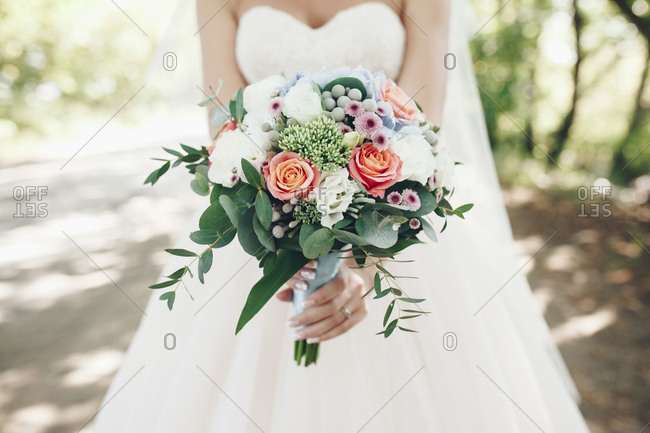Caucasian bride holding bouquet of flowers outdoors