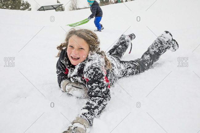 Laughing girl laying in snow in winter