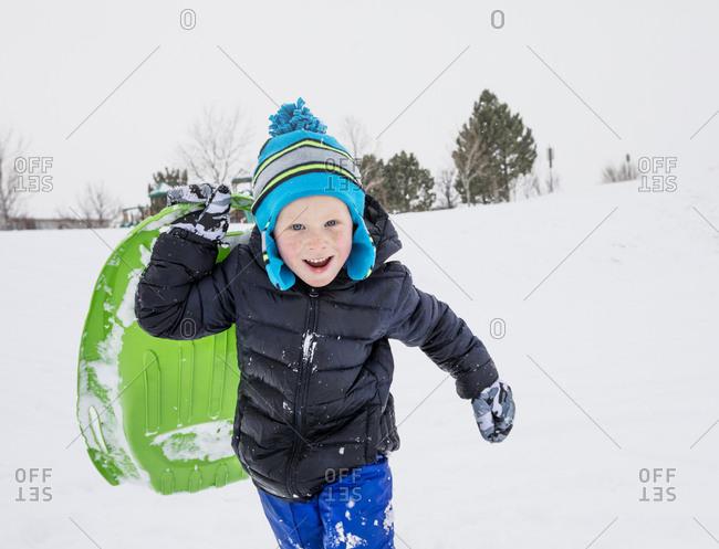 Smiling boy running with toboggan in winter