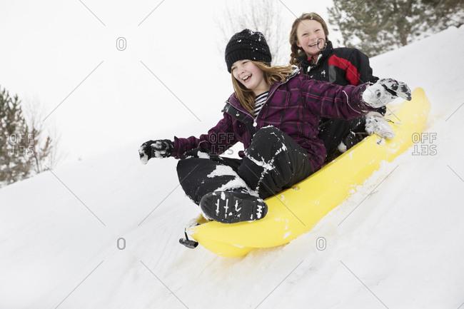 Smiling girls sliding in toboggan on hill in winter