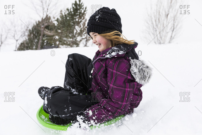 Smiling girl sliding on toboggan in snow