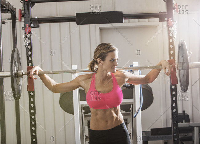 Woman lifting barbell in gymnasium
