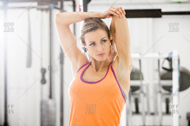 Woman stretching arm in gymnasium