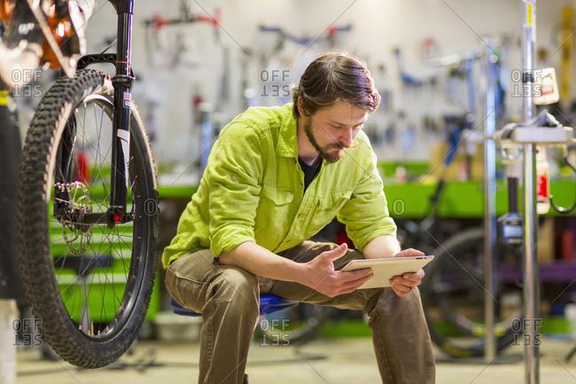 Caucasian worker using digital tablet in bicycle shop