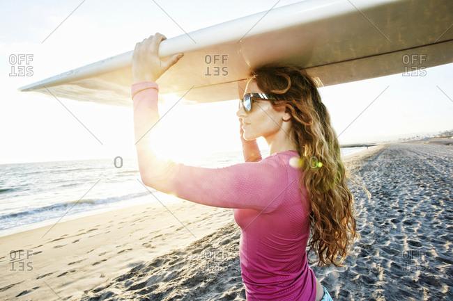 Caucasian woman carrying surfboard on beach