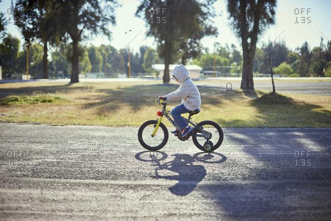 Hispanic boy riding bicycle with training wheels