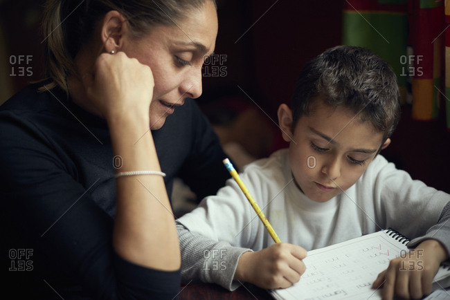 Hispanic mother watching son practicing writing alphabet