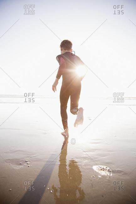 Caucasian boy wearing wetsuit running on sunny beach