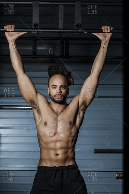 Mixed Race man holding bar in gymnasium
