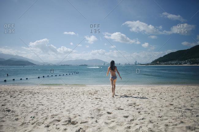 Caucasian woman wearing bikini running on beach