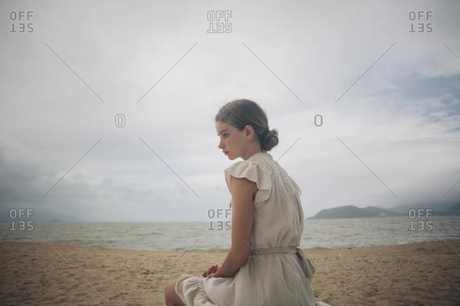 Caucasian women wearing dress sitting on beach