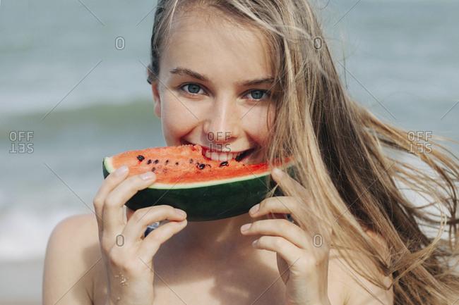 Caucasian woman eating watermelon on beach