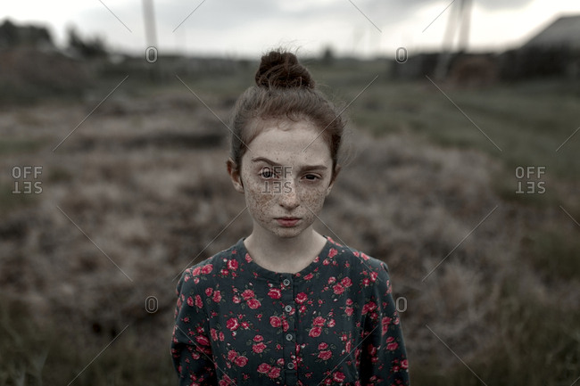 Caucasian girl with freckles raising eyebrow in field