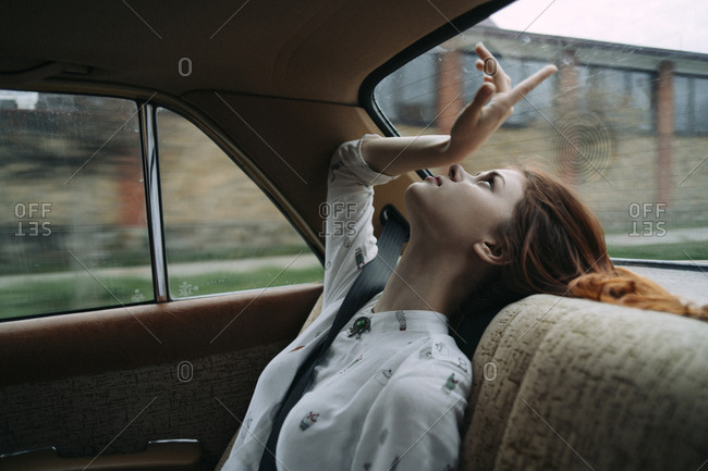 Caucasian woman in back seat of car looking up