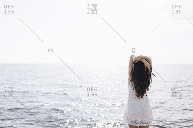 Woman standing near ocean with arms raised