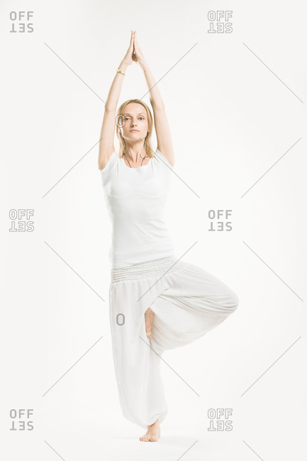 Woman in all white standing in a yoga tree pose