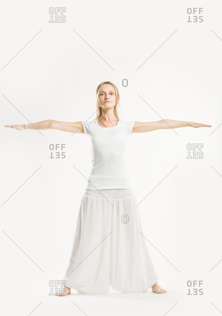 Woman standing with her arms raised and legs out in a yoga position