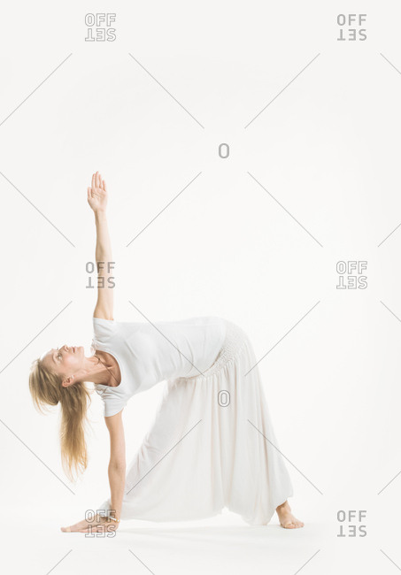 Woman in all white standing in a yoga triangle pose