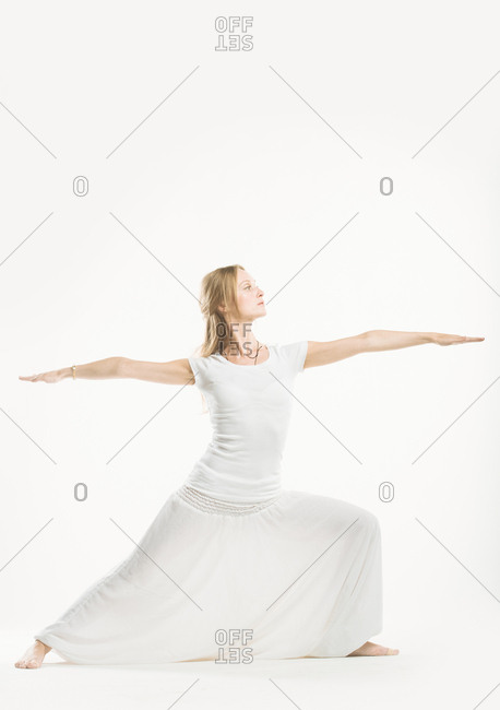 Woman in all white performing a yoga warrior pose