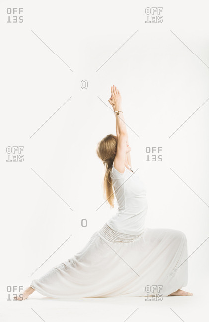 Woman in all white standing in a lunge yoga pose