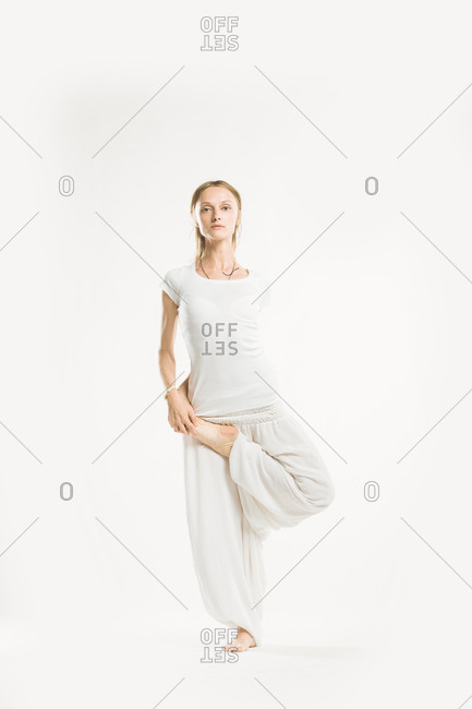 Woman standing in a yoga pose with her leg bent in front of her