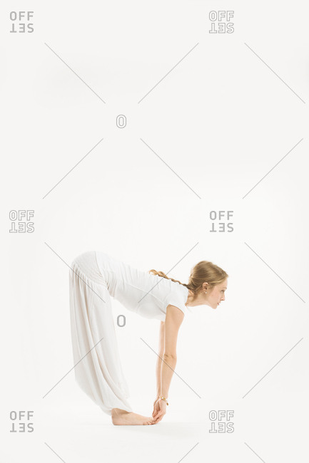 Woman bending forward and grabbing beneath her toes