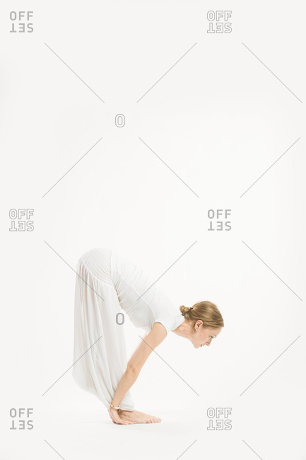 Woman bending forward with her palms flat beside her feet