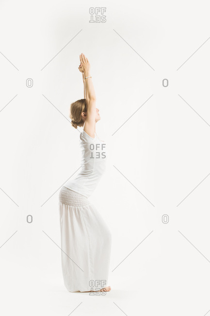 Woman standing in a yoga pose with her hands clasped above her head