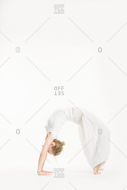 Woman in all white performing a wheel yoga pose