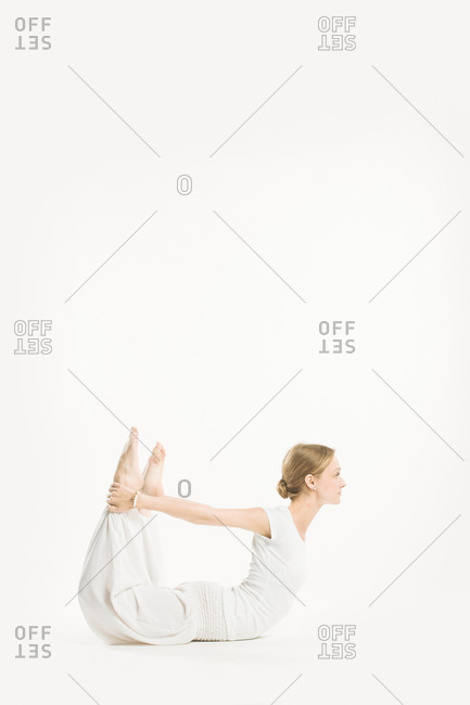 Woman in all white performing a bow yoga pose