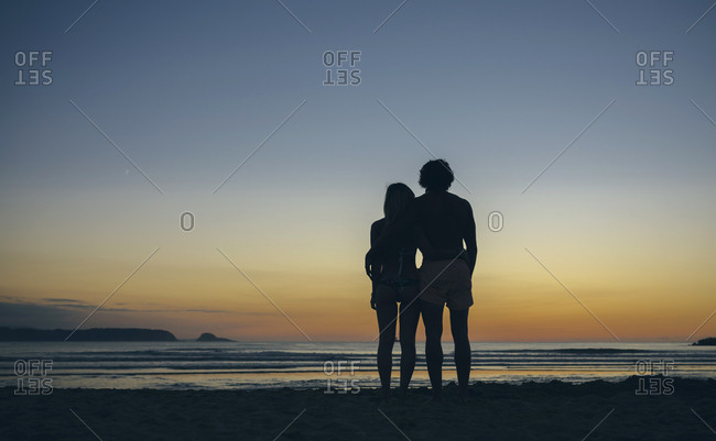 Young couple watching the sunset on the beach