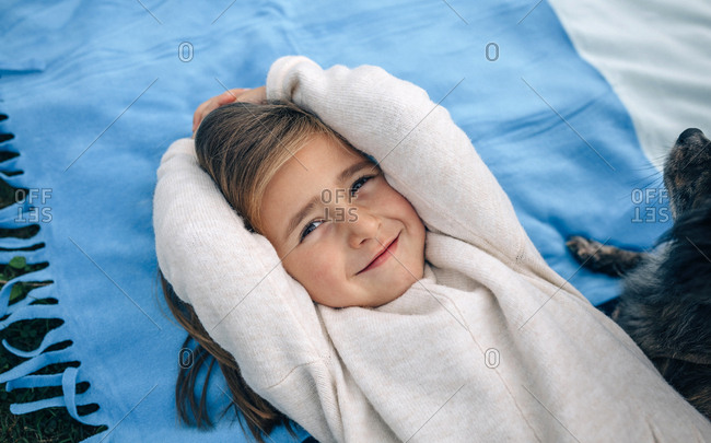 Portrait of smiling girl lying on blanket with dog
