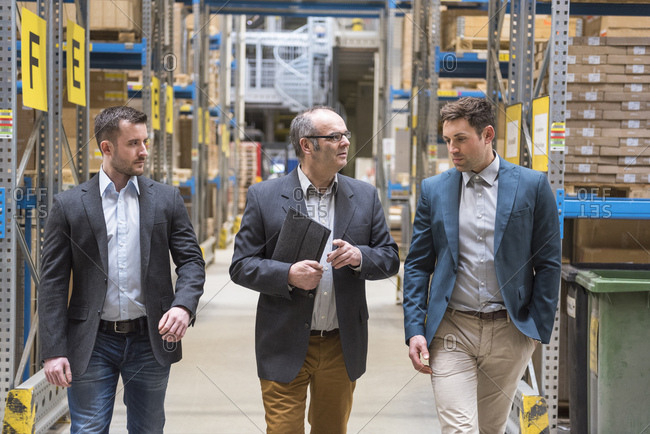 Three men walking in factory warehouse