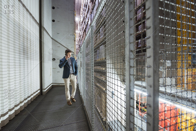 Man in automatized high rack warehouse talking on cell phone