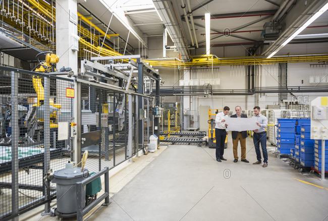 Three men with blueprint talking in factory shop floor