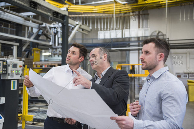 Three men with blueprint talking in factory shop floor