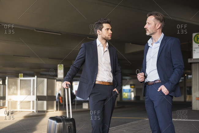 Two businessmen with rolling suitcase standing at bus terminal