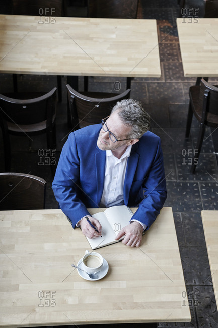 Mature businessman in cafe writing in diary