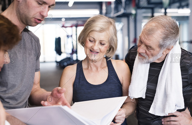 Group of fit seniors and personal trainer in gym looking in folder