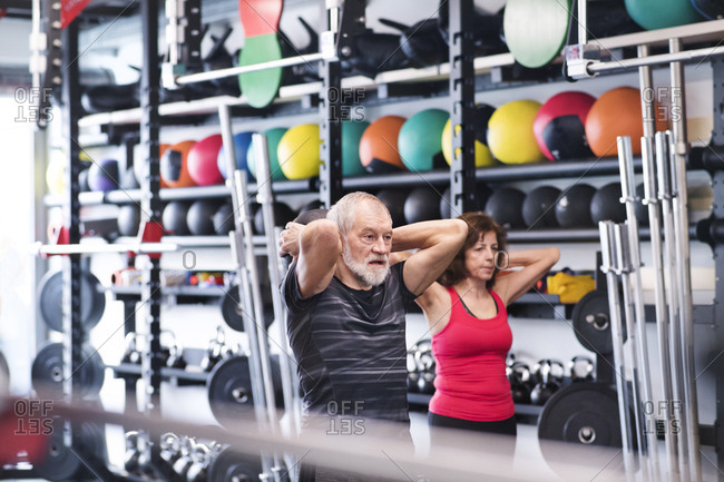 Senior man and woman in gym exercising with medicine balls