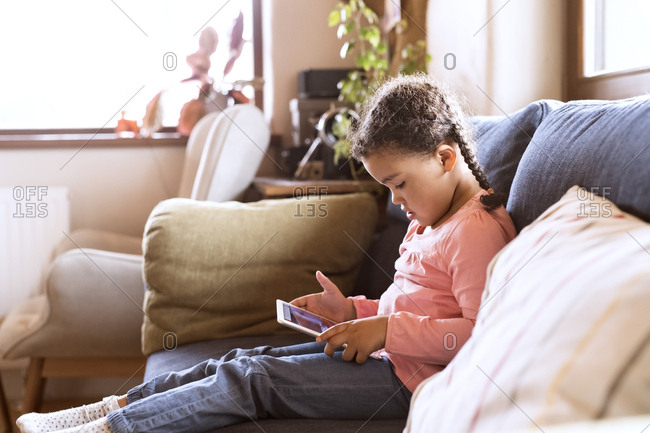 Little girl using sitting tablet- sitting on couch