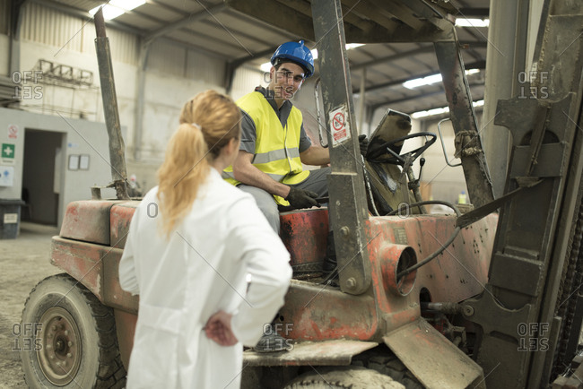 Scientist talking to a forklift driver in a factory