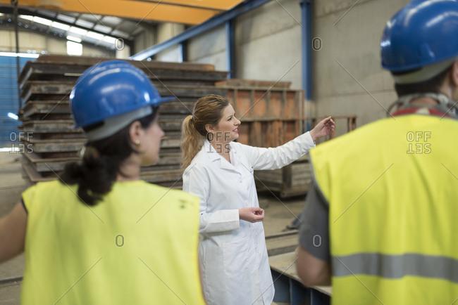 Scientist briefing workers in factory