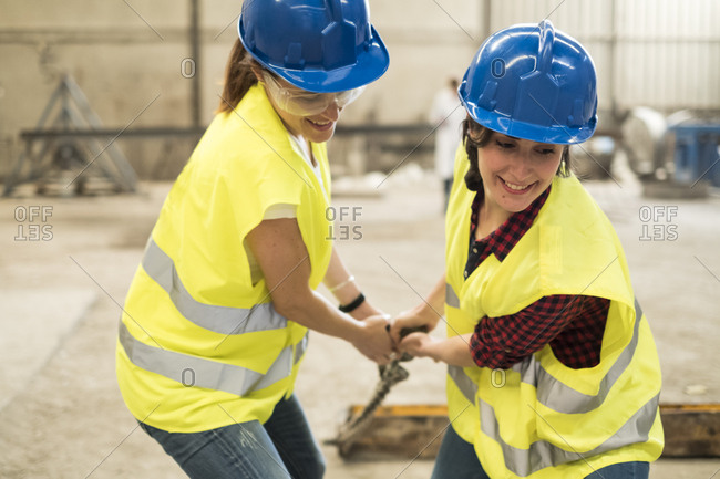 Female skilled workers in concrete factory pulling machine part
