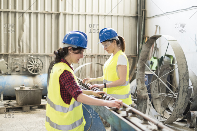 Female skilled workers in concrete factory adjusting machine