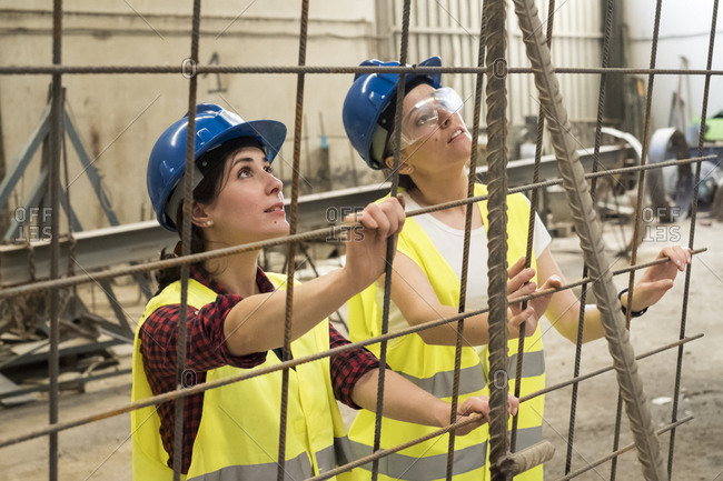 Female skilled workers in concrete factory setting up iron reinforcement