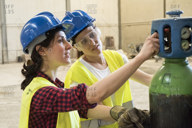 Female skilled workers in concrete factory adjusting welding torch