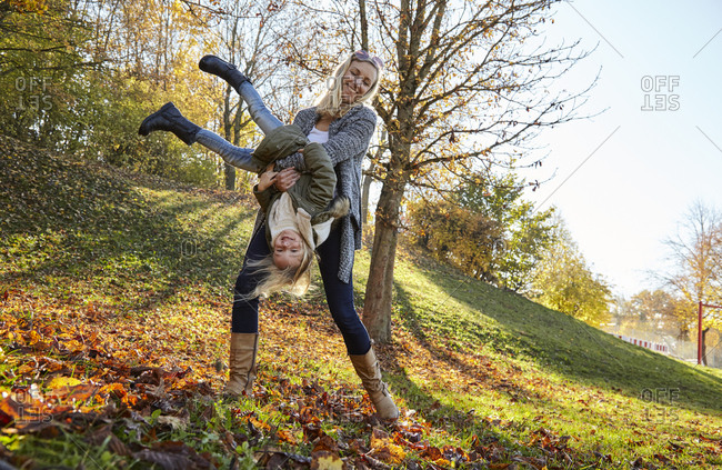 Mother and daughter playing in park in autumn