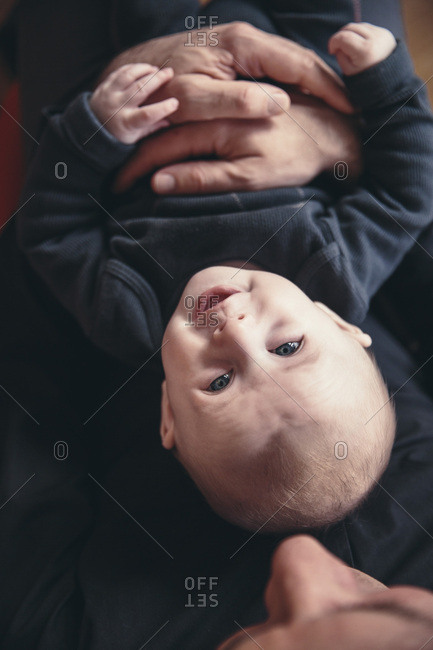 Three-month-old baby being held by father as seen from above